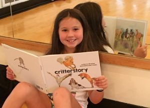 A young girl reads 'critterstory' a children's picture book ©ponderover publishing, llc