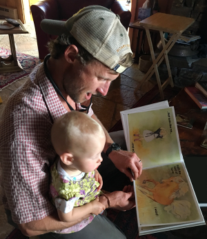 Father reading 'I want a Palomino' in critterstory book to his young daughter.