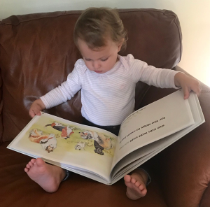 A young two year old girl loves reading about the dogs in critterstory.